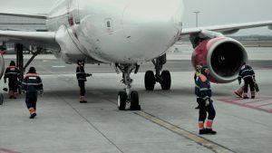 Příslušní zaměstnanci provádějí předepsané kroky, když letadlo zastaví u stojánky.