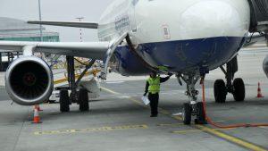 Začíná se s otevřením zavazadlového prostoru. Všimněte si bezpečnostních kuželů před motory letadla.