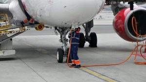 Technik připojuje letadlo k externímu zdroji napájení